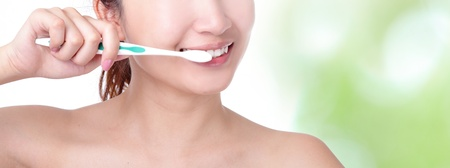 oral care: close up of a woman mouth and brushing her teeth with nature green background, model is a asian girl