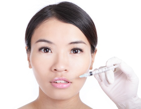 Beautiful woman receiving a injection in her lip isolated on white background, model is a asian beauty Stock Photo - 13577992