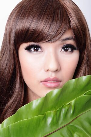 Woman face and green leaf, model is a asian beauty photo