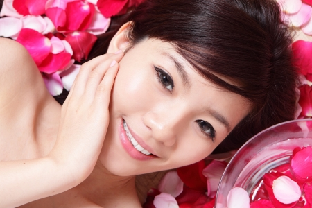 Asian beauty Girl smiling face and rose petal background, and touching her face photo