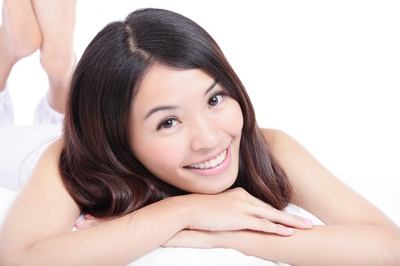 dental smile: Beautiful young girl smile face close up and lying on bed over white background, model is a asian woman