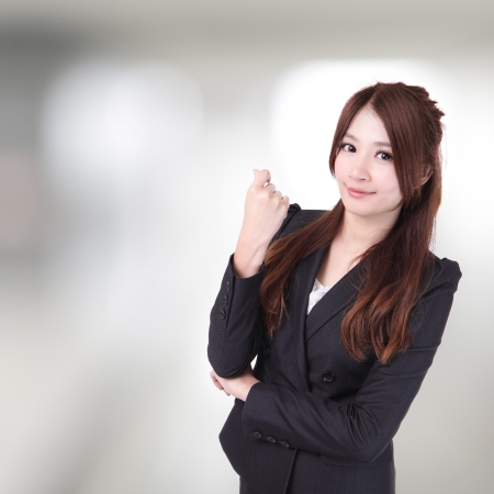 confident business woman in the office with smile face close up, model is a asian beauty photo