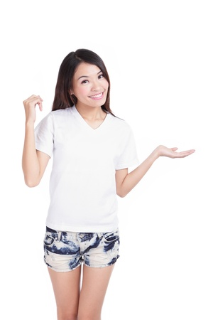 introduce: Young Girl happy smile show white T-Shirt with hand introduce something isolated on white background  designer could add any thing on empty copy space , model is a asian woman Stock Photo