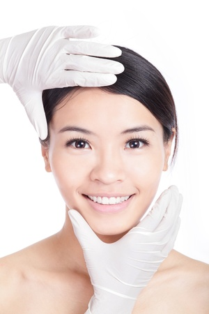 Plastic surgery touching the beautiful woman face. Isolated on white background, model is a asian beauty photo
