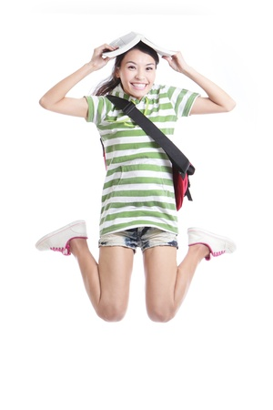 Excited student girl jumping with book and bag in full length - isolated over white background, model are asian people photo