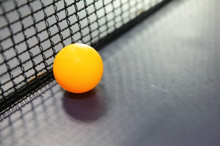 Orange table tennis ball on blue table with net photo