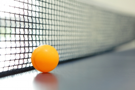 Orange table tennis ball on blue table with net Stock Photo - 13873277