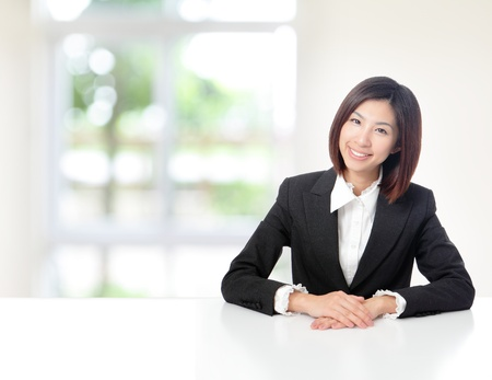 copyspace corporate: Young Business woman smile face close up and sit at company office with white table, window outside are green background, model is a asian beauty