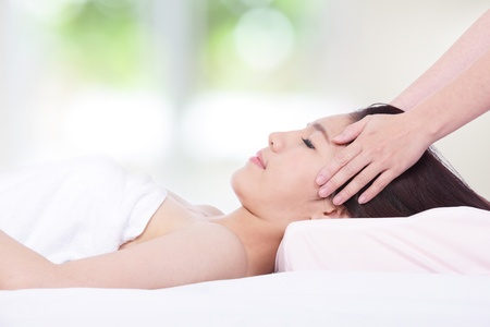 Portrait of a woman lying on a massage table in a health spa with nature green background, model is a asian girl photo