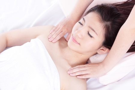 woman lying on a massage table in a health spa, model is a asian girl photo