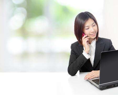 젊은 아름 다운 비즈니스 여자가 휴대 전화를 말하기와 자연 녹색 창 사무실에서 컴퓨터를 사용하는 모델은 아시아의 아름다움