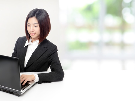 Young Business woman using computer and sit at company office with white table, window outside are green background, model is a asian beauty photo