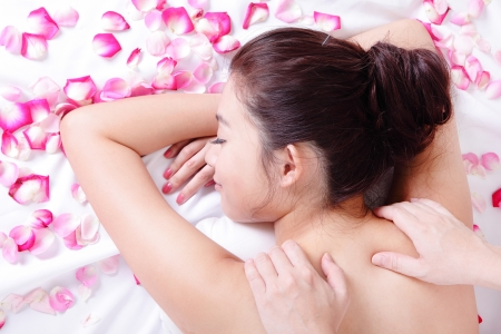 head and shoulder: Beautiful woman getting massage and spa treatment with rose background, model is a asian beauty