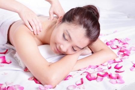 masaje corporal: Sonrisa hermosa de la mujer recibiendo masajes y tratamientos de spa con fondo rosa, modelo es una belleza asi�tica