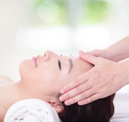 head massage: close up of Beautiful asian woman enjoy receiving face and head massage at spa with nature green background Stock Photo