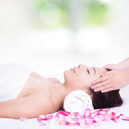 tratamiento facial: Hermosa mujer asi�tica disfrutar de la cara y recibir masaje en la cabeza en el spa con la naturaleza de fondo verde Foto de archivo