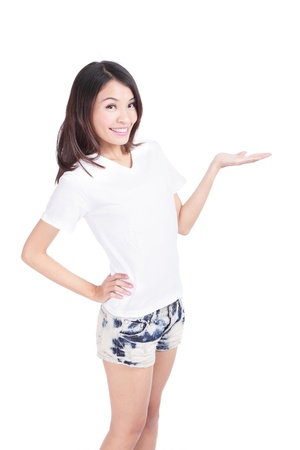 introduce: Young Girl happy smile show white T-Shirt with hand introduce something isolated on white background (designer could add any thing on empty copy space), model is a asian woman