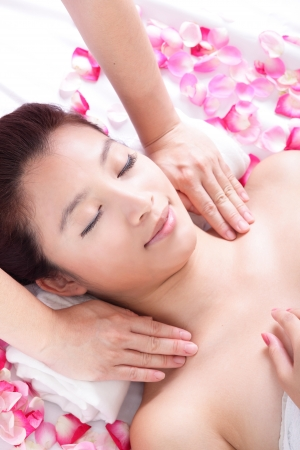 Beautiful woman smile getting massage and spa treatment with rose background, hand touch shoulders, model is a asian beauty photo