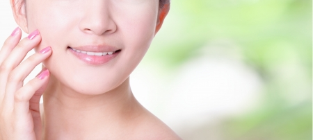 care for: charming woman smile mouth and lips with health teeth close up on nature green background, concept for skincare and dental health care , model is a asian girl Stock Photo