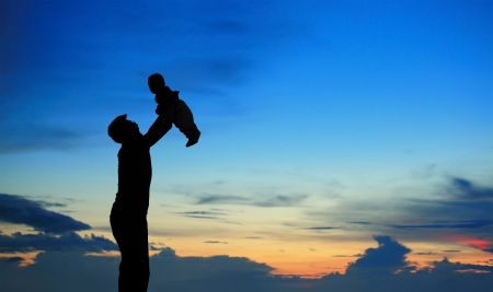 Silhouette of father and child on beautiful summer sunset - family photo