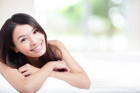 sonrisa: La cara con Encanto sonrisa de mujer de cerca y ella acostada en la cama en la ma�ana con la naturaleza de fondo verde, modelo es una muchacha asi�tica