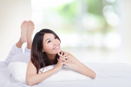 rest in peace: Waiting for the dream come true, Charming woman lying on the bed and looking to empty copy space in the morning, model is a asian girl