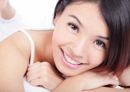 close up of Beautiful young woman smiling face with health teeth. Isolated over white background, model is a asian beauty photo