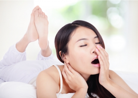 sleeping room: young attractive woman yawning in bed in the morning with nature green background, model is a asian girl