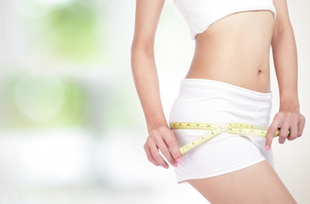 close up of Young Woman measuring perfect shape of beautiful hips. Healthy lifestyles concept, with green background Stock Photo - 14730964