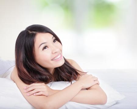 Okouzlující žena úsměv tvář zblízka a ona leží na posteli v dopoledních hodinách s přírodní zelené pozadí, model je asian girl