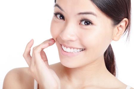 gezicht: Mooie jonge lachende vrouw de hand te raken haar gezicht en mond, lippen, tanden. Geà ¯ soleerd op witte achtergrond, model is een Aziatisch meisje