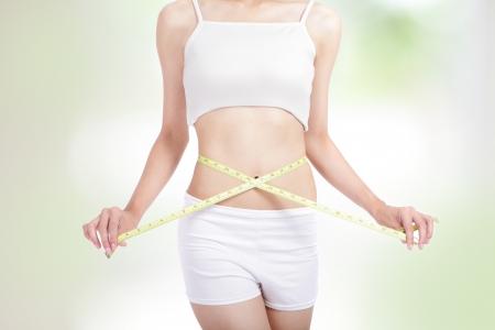 자연 녹색 배경 건강 한 생활 개념 미소로 아름다운 허리의 형태를 측정하는 여자, 모델은 아시아의 아름다움