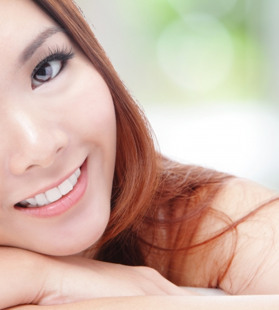 asia nature: portrait of half face young woman smile with health teeth and charming smile on green background, mode is asian girl Stock Photo