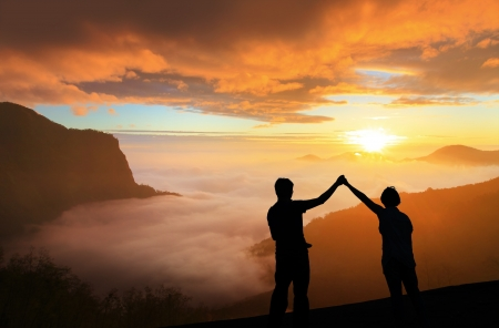 silhouette of Young family happy look sunrise on the top mountain photo