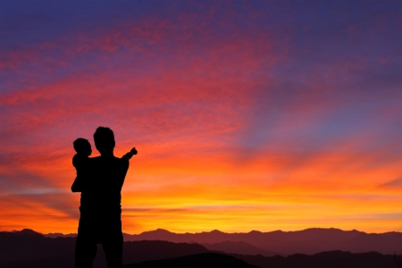 The silhouette of family (Father and child) watching the sunrise and hand finger point to sun with mountain Stock Photo