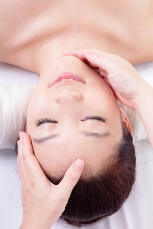 Beautiful asian woman enjoy receiving face and head massage at spa center, view from high angle photo
