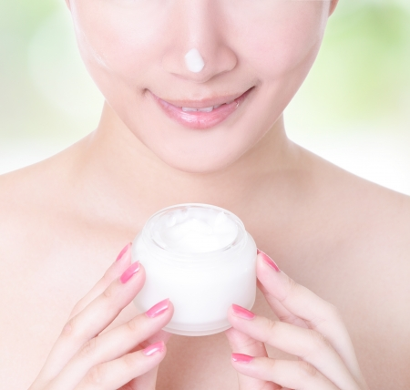 Close up of asian woman smile with moisturizer cream on face on green background photo