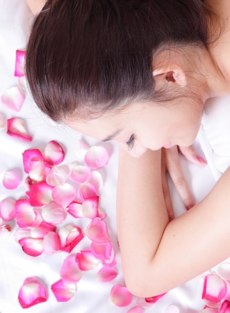 Beautiful woman smile getting massage and spa treatment with rose background, model is a asian beauty photo