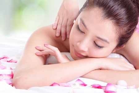 face massage: Beautiful young girl with attractive face having a massage for shoulder on resort green background, model is a asian woman