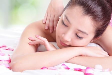 massaggio: Bella ragazza con la faccia attraente avendo un massaggio di spalla su sfondo verde resort, il modello � una donna asiatica