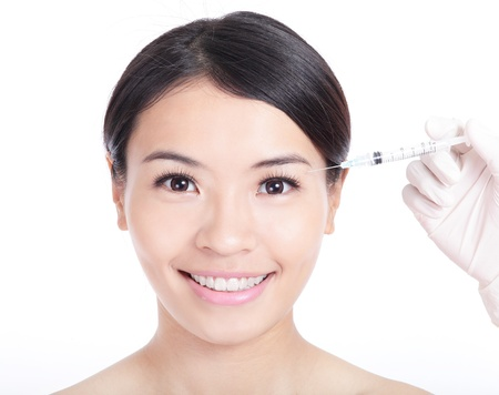 Cosmetic injection surgery to the pretty woman face isolated on white background, model is a asian beauty