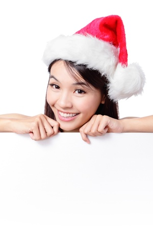 Santa girl happy smile face behind blank sign billboard. Advertising photo of young smiling Christmas woman in Santa hat showing paper sign. Asian female model isolated on white background photo