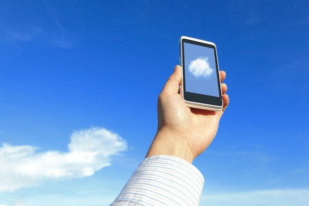 Business man holding his mobile phone with white cloud and blue sky, concept for cloud computing photo