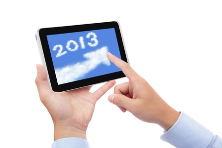 Tablet PC computer with 2013 happy New Year in cloud text and blue sky isolated on white background. concept for cloud computing photo