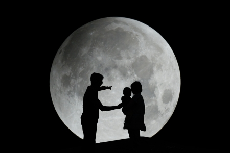 Silhouette of father, mother and child with moon in the night - family photo