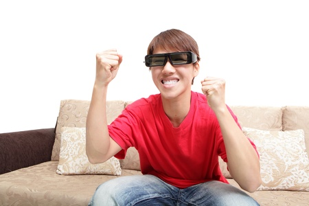 Young man wearing 3d glasses excited happy watch tv at home, model is a asian people photo