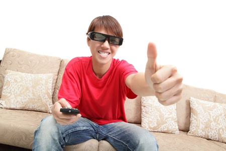 Young man wearing 3d glasses excited happy watch tv and thumb up sign at home, model is a asian people photo