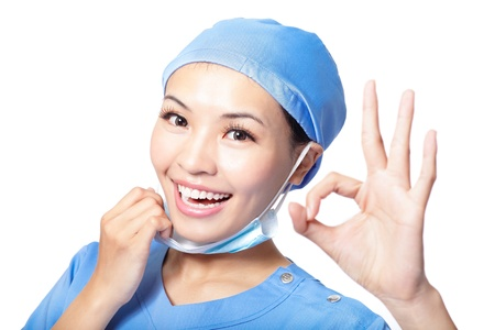 ok sign: Young woman doctor or nurse giving ok gesture taking off the surgeon mask smiling isolated on white background, Asian female model Stock Photo
