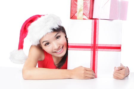 Santa girl holding christmas gift. Young happy woman in santa hat smile showing Christmas present isolated on white background. model is a asian beauty photo