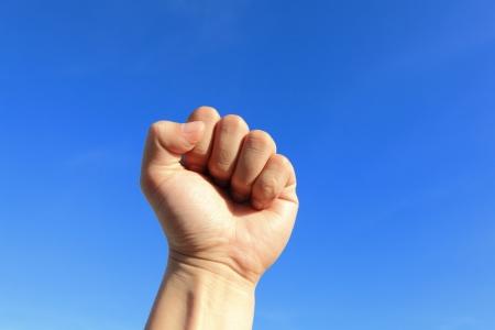 manos levantadas al cielo: Pu�o cerrado en el aire con el cielo azul Foto de archivo